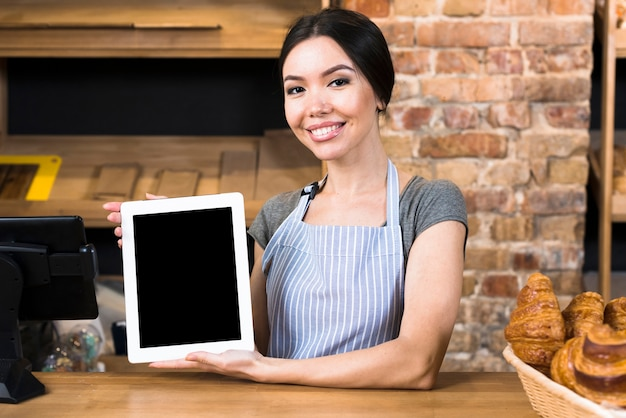Lächelndes porträt eines jungen weiblichen bäckers, der die digitale tablette steht am bäckereizähler hält