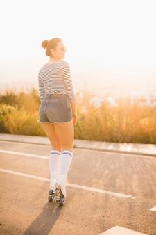 Lächelndes porträt eines jungen weiblichen schlittschuhläufers, der auf straße steht