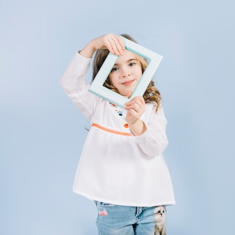 Lächelndes porträt eines mädchens, das blauen grenzrahmen vor ihrem gesicht gegen blauen hintergrund hält