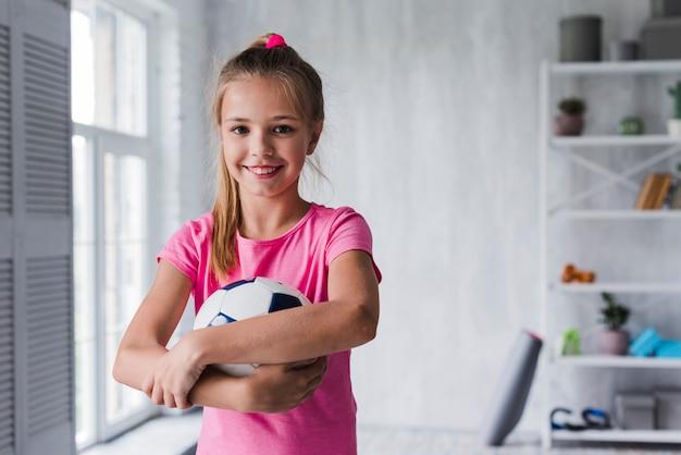 Lächelndes porträt eines mädchens, das fußball hält