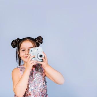 Lächelndes porträt eines mädchens, das mit retro- sofortiger kamera gegen blauen hintergrund fotografiert