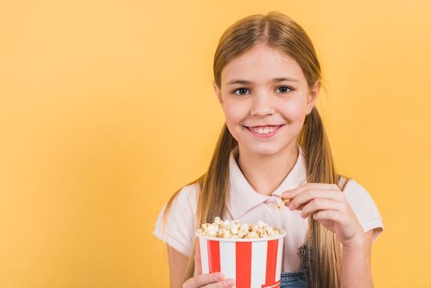 Lächelndes porträt eines mädchens, das popcorneimer gegen gelben hintergrund hält