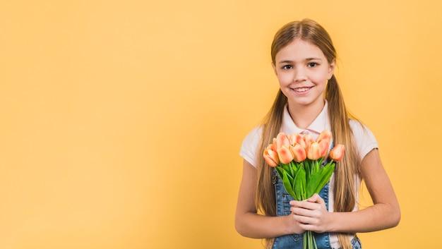 Lächelndes porträt eines mädchens, halten orange tulpen in der hand gegen gelben hintergrund
