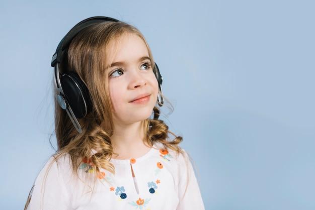 Lächelndes porträt eines mädchens mit dem kopfhörer, der weg gegen blauen hintergrund schaut