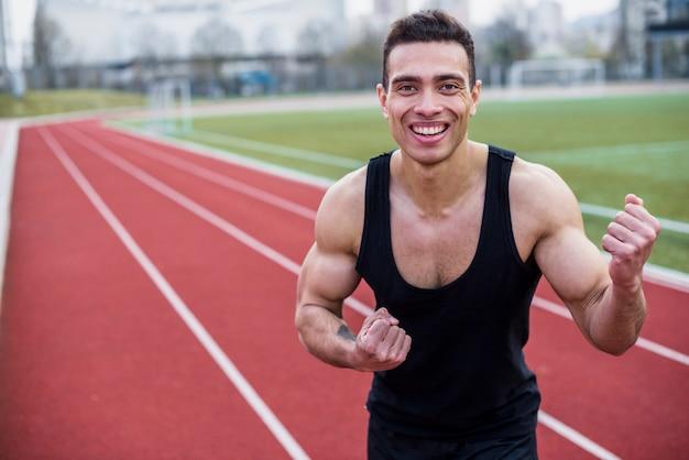 Lächelndes porträt eines männlichen athleten, der seine faust zusammenpreßt, nachdem rennen gewonnen worden ist
