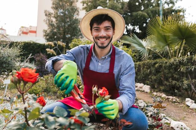 Lächelndes porträt eines männlichen gärtners, der die rosenblume mit gartenscheren beschneidet