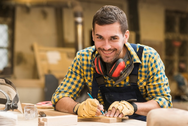 Lächelndes porträt eines männlichen tischlers, der maß mit machthaber und bleistift auf holzklotz nimmt