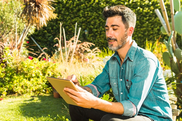 Lächelndes porträt eines mannes, der digitale tablette im park verwendet