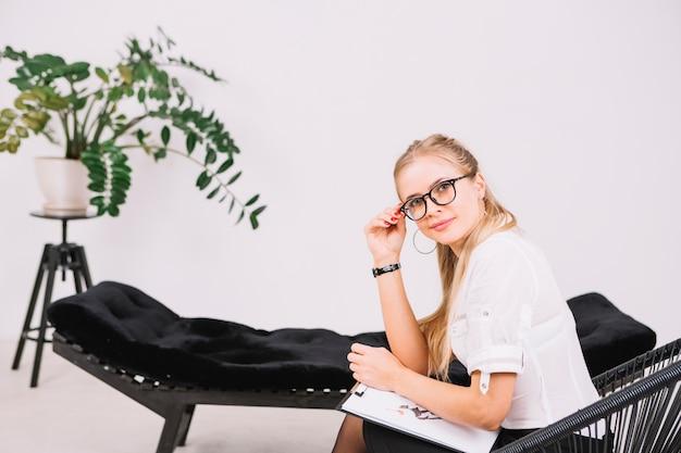 Lächelndes porträt eines schönen psychologen, der auf stuhl mit klemmbrett im büro sitzt