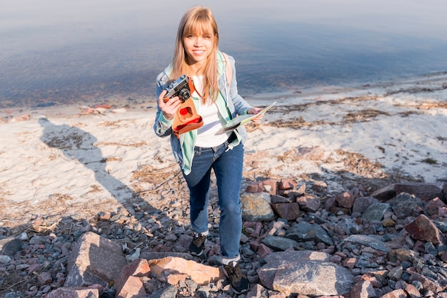 Lächelndes porträt eines weiblichen reisenden, der karte und kamera am strand hält
