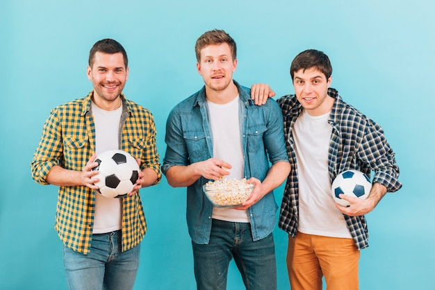Lächelndes porträt von den freunden, die fußballspiel gegen blauen hintergrund aufpassen