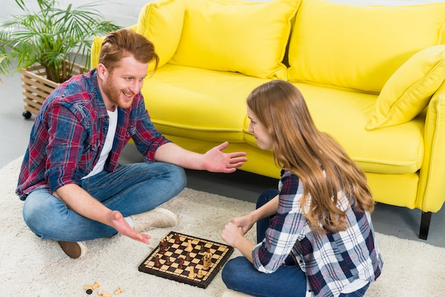 Lächelndes porträt von den jungen paaren, die auf dem teppich spielt das schach sitzen
