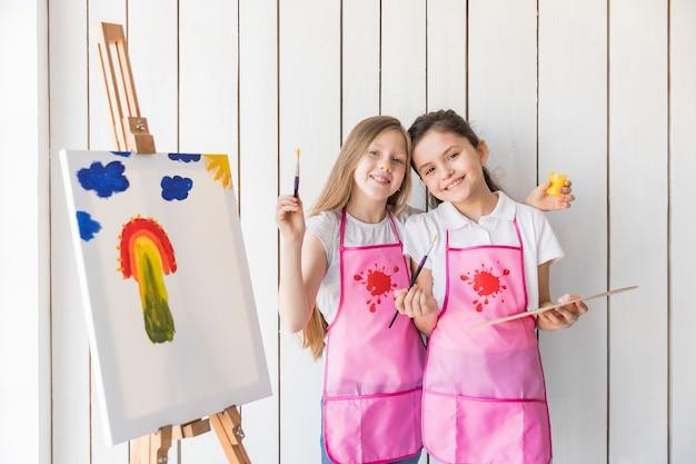 Lächelndes porträt von den mädchen, die den malerpinsel und -palette stehen nahe dem gestell mit gezogenem malen halten