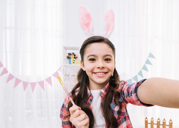 Lächelndes porträt von den tragenden häschenohren einer tochter, die selfie nehmen