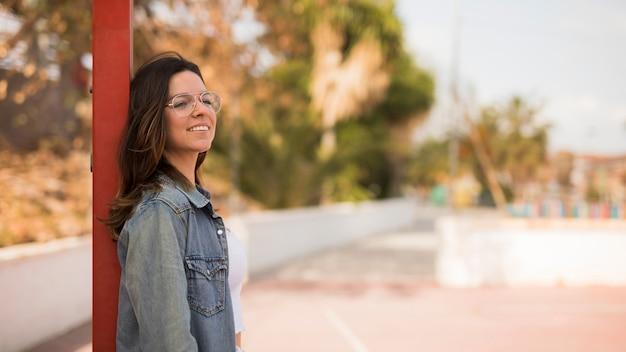 Lächelndes porträt von tragenden brillen einer jungen frau, die auf pfosten sich lehnen