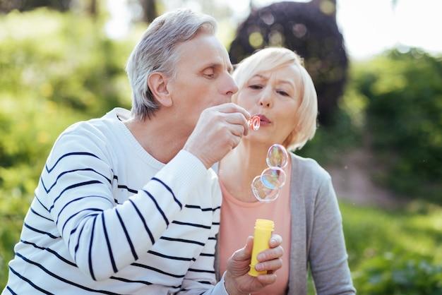 Lächelndes positives älteres paar, das sich umarmt und seifenblasen macht, während es freizeit im park genießt und freude ausdrückt