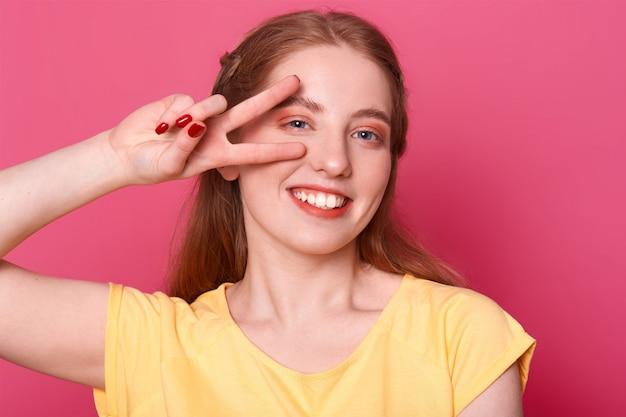 Lächelndes positives modell stellt lokalisiert über hellrosa hintergrund im studio mit siegeshand nahe ihrem rechten auge dar, tragendes gelbes t-shirt