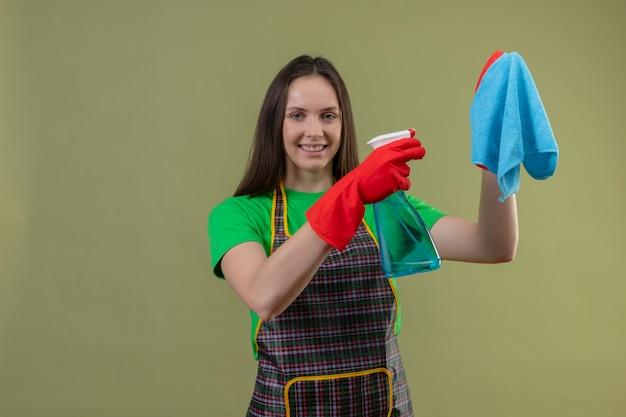 Lächelndes putzendes junges mädchen, das uniform in den roten handschuhen hält, die reinigungsspray heraushalten, um auf ihrer hand auf lokalisiertem grünem hintergrund lappen