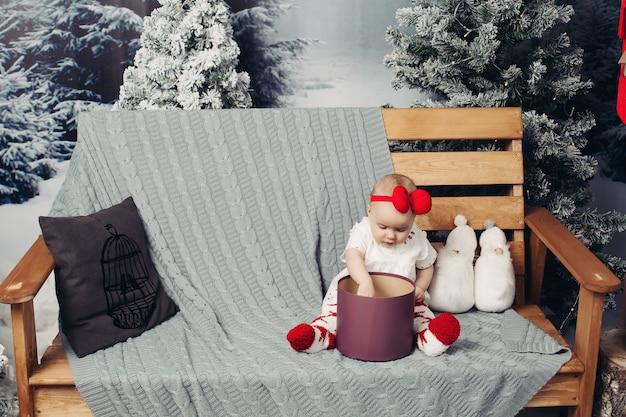 Lächelndes reizendes baby im netten kleid mit dem stirnband, das auf bank mit vielen weihnachtsgeschenken sitzt