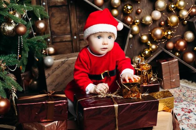 Lächelndes reizendes baby im netten kleid mit sankt hut, der auf bank mit vielen weihnachtsgeschenken sitzt
