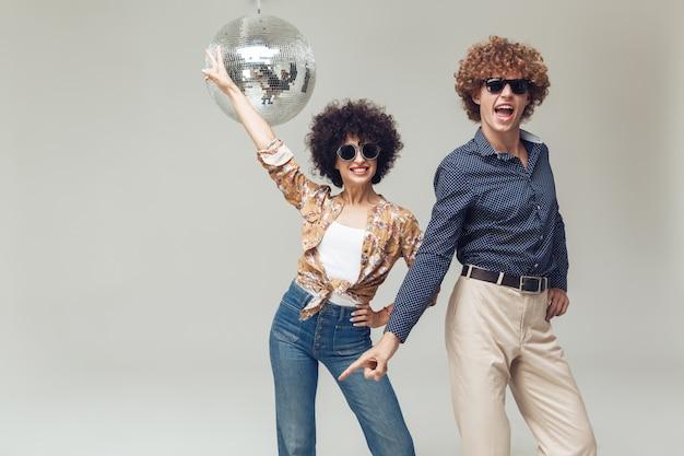 Lächelndes retro-liebespaar nahe der disco-kugel.