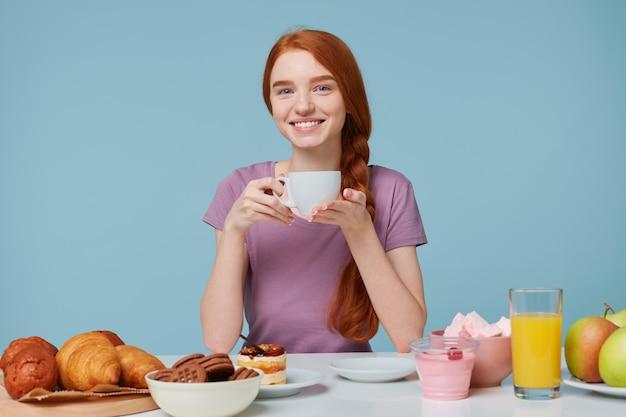 Lächelndes rothaariges mädchen mit geflochtenem haar, das an einem tisch sitzt, hält weiße tasse mit köstlichem getränk in den händen