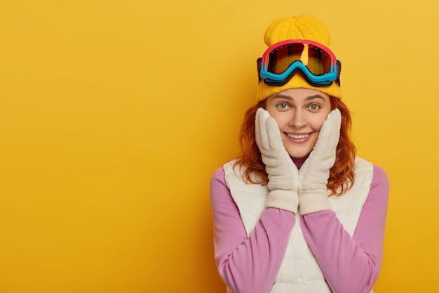 Lächelndes rothaariges snowboardermädchen hat glücklichen ausdruck, berührt wangen, lokalisiert über gelbem hintergrund