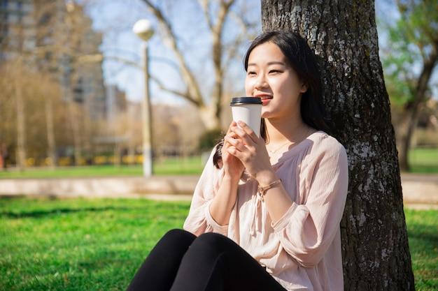 Lächelndes ruhiges mädchen, das mitnehmerkaffee im stadtpark trinkt