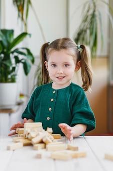 Lächelndes schlaues süßes kind in grünem kleid und gebrochenem hölzernem jenga-turm auf einem tisch indoor-aktivitäten