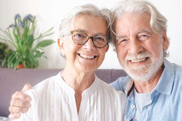 Lächelndes schönes älteres paar, das zu hause auf der couch sitzt und in die kamera schaut