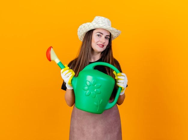 Lächelndes schönes gärtnermädchen, das uniform und gartenhut mit handschuhen hält, die bewässerungsdose halten