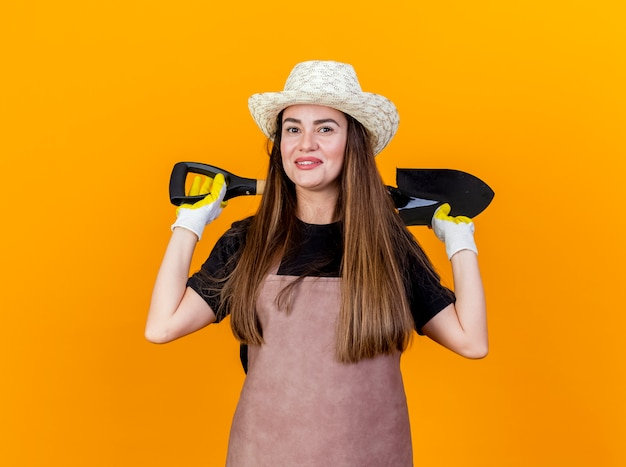 Lächelndes schönes gärtnermädchen, das uniform und gartenhut mit handschuhen hält, die spaten auf hinter hals lokalisiert auf orange hintergrund halten