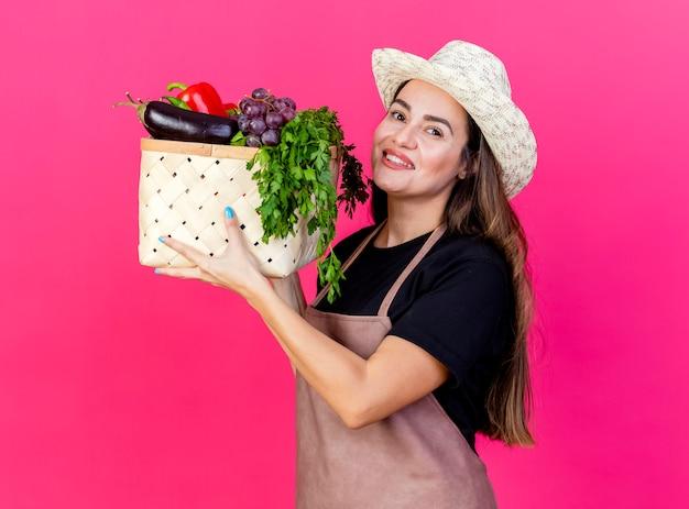 Lächelndes schönes gärtnermädchen in der uniform, die den gartenhut trägt, der gemüsekorb lokalisiert auf rosa hintergrund anhebt