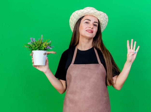 Lächelndes schönes gärtnermädchen in der uniform, die gartenhut hält, der blume im blumentopf hält, der vier lokalisiert auf grünem hintergrund zeigt