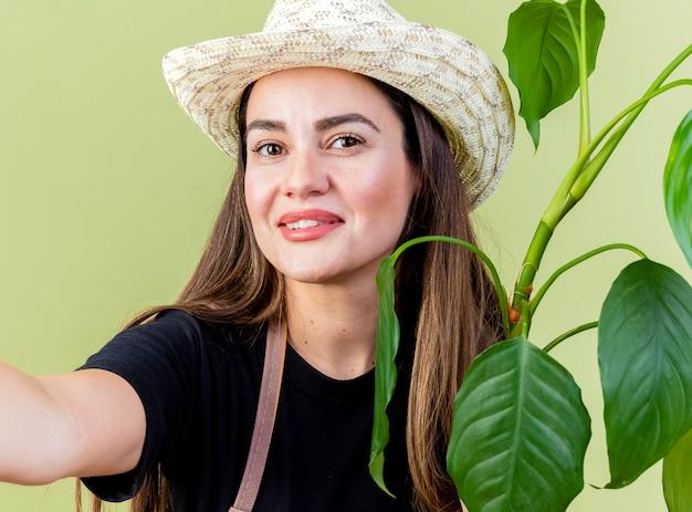 Lächelndes schönes gärtnermädchen in der uniform, die gartenhut-haltepflanze mit kamera lokalisiert auf olivgrün trägt