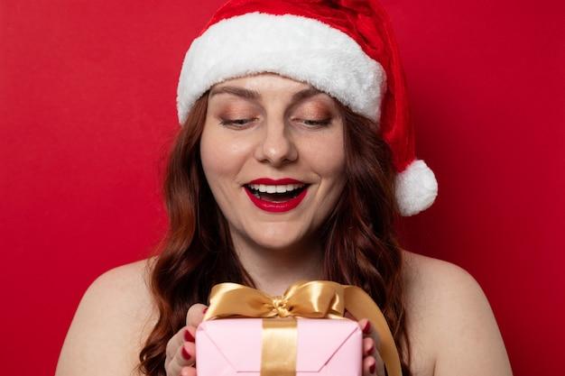 Lächelndes schönes gelocktes rothaariges mädchen in sankt-hut, der glückliche gefühle ausdrückt und präsentkarton mit satinbandbogen auf einem rot hält. weihnachtseinkaufstag