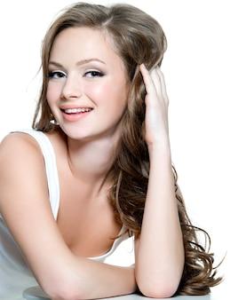 Lächelndes schönes gesicht des teenager-mädchens mit sauberer haut - lokalisiert auf weiß