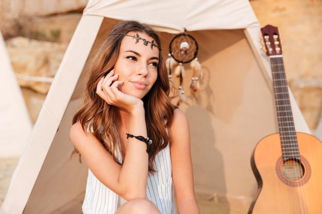 Lächelndes schönes hippie-mädchen, das im strandzelt auf dem campingplatz ausruht