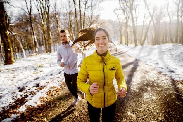 Lächelndes schönes junges gesundes mädchen, das mit einem trainer in sportbekleidung durch den wald am sonnigen wintermorgen läuft.