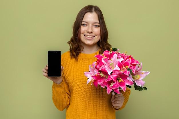 Lächelndes schönes junges mädchen, das blumenstrauß mit telefon hält