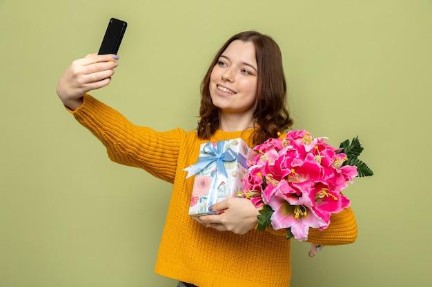 Lächelndes schönes junges mädchen mit blumenstrauß mit geschenk machen ein selfie
