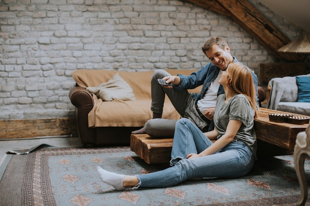 Lächelndes schönes junges paar, das sich entspannt und zu hause fernsieht