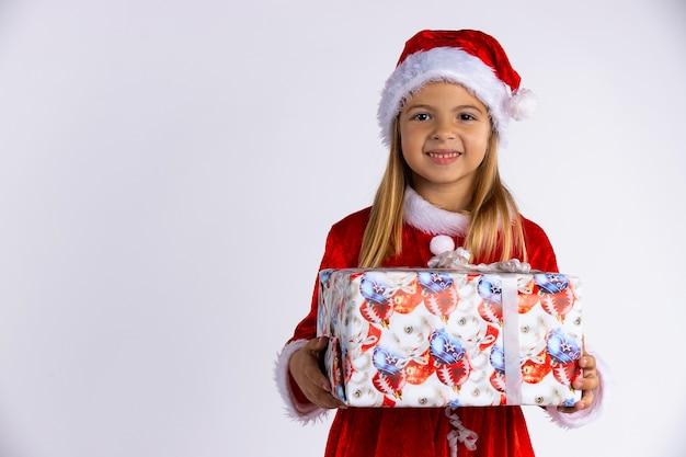 Lächelndes schönes kaukasisches mädchen im roten hut und im kostüm des weihnachtsmanns, das weihnachtsgeschenk in der hand hält