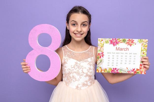 Lächelndes schönes kleines mädchen am glücklichen frauentag, der die nummer acht mit kalender hält