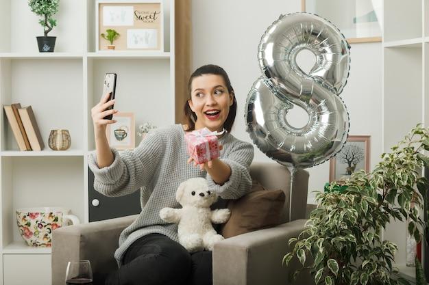 Lächelndes schönes mädchen am glücklichen frauentag mit geschenk machen ein selfie, das auf einem sessel im wohnzimmer sitzt