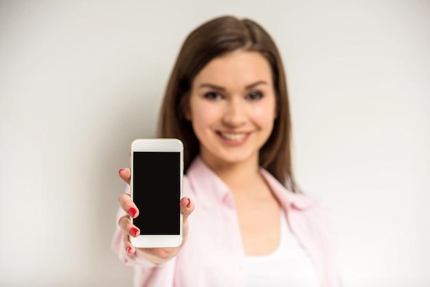 Lächelndes schönes mädchen, das einen leeren intelligenten telefonschirm zeigt.