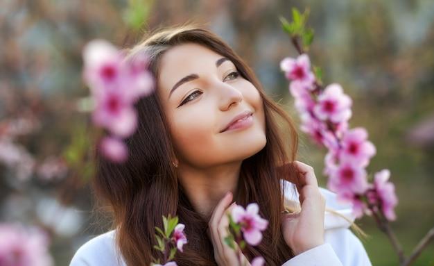 Lächelndes schönes mädchen, das nahe einem pfirsichbaum während des sonnenuntergangs steht. glückliches gesicht. frühlingszeit.