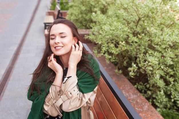 Lächelndes schönes mädchen in der stadt. wind, der langes haar der glücklichen jungen frau entwickelt. porträt eines niedlichen mädchens mit geschlossenen augen. speicherplatz kopieren