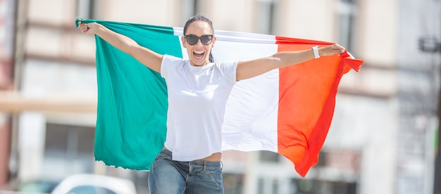 Lächelndes schönes mädchen in sonnenbrille und weißem t-shirt hält italienische flagge auf einer feiernden straße.