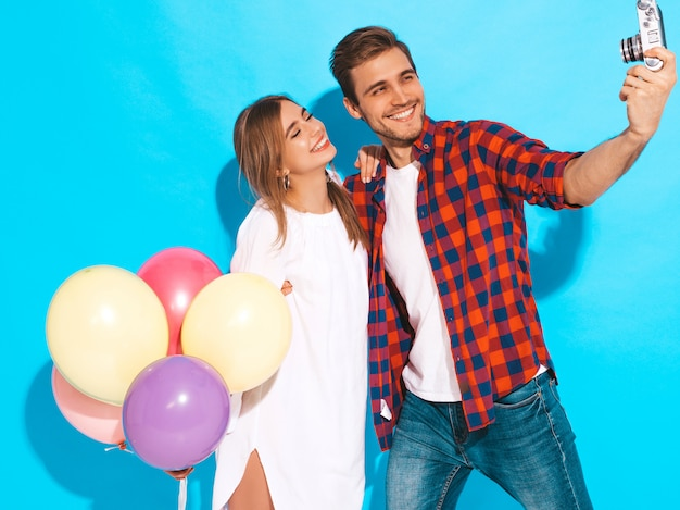 Lächelndes schönes mädchen und ihr hübscher freund, die bündel bunte ballone hält. glückliches paar, das foto selfie von selbst auf retro- kamera macht. alles gute zum geburtstag
